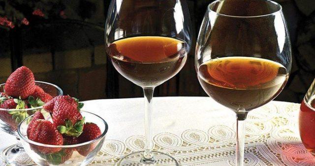 вино в бокалах и ягоды клубники на столе