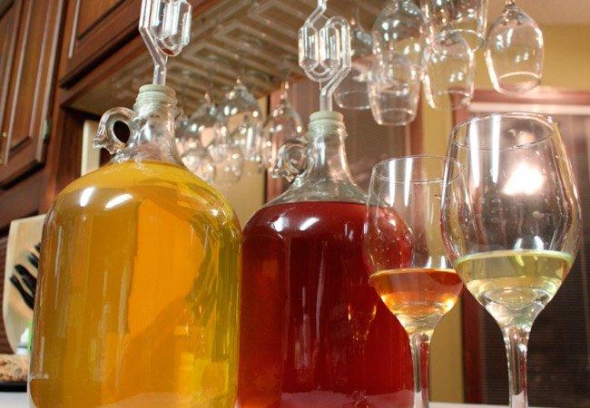 Разное вино в бутылках и бокалах
