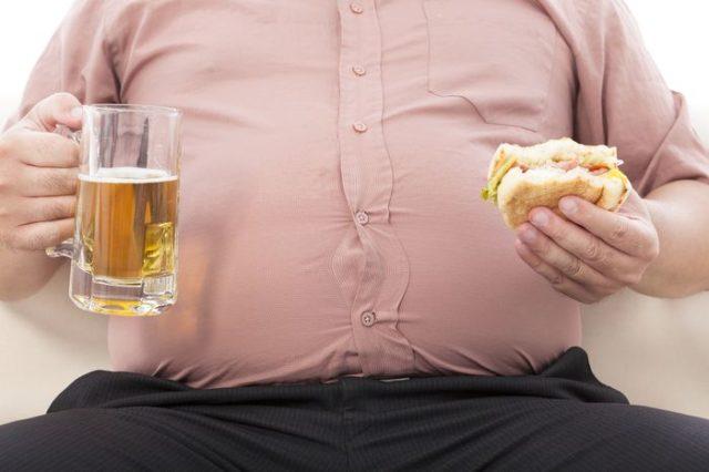 мужчина держит в руках пиво и гамбургер