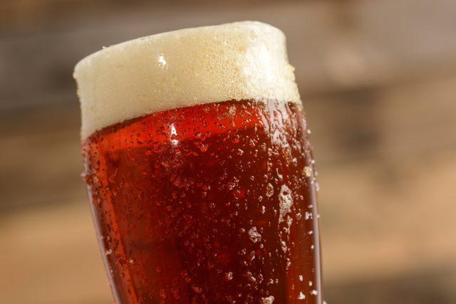 Бокал красного пива с пеной