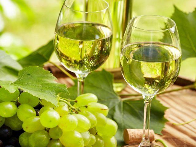 Бокалы с вином и гроздь винограда