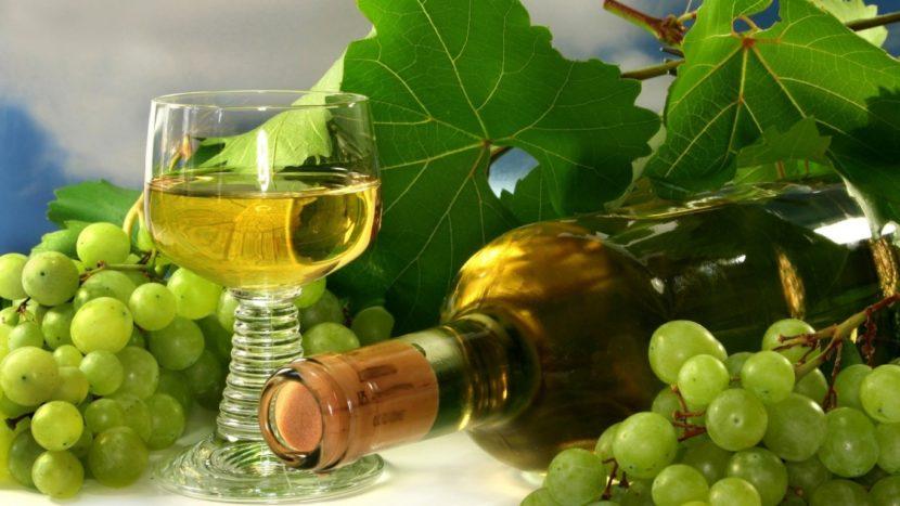 Бутылка и бокал с вином на фоне гроздей винограда