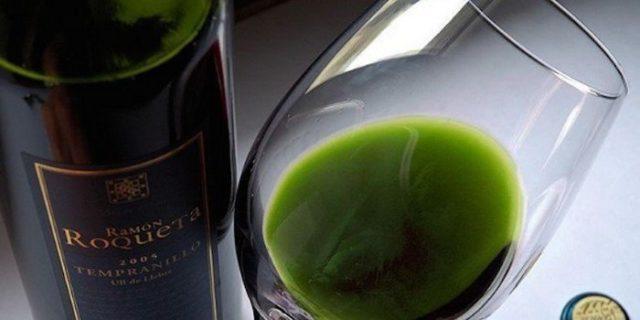 Бутылка и бокал с напитком зеленого цвета