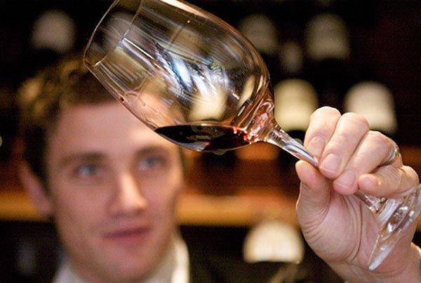 Мужчина рассматривает вино в бокале