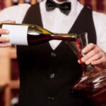 Сомелье переливает вино из бутылки в декантер