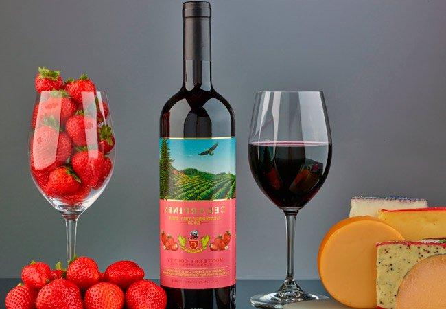 булылка и бокал клубничного вина и ягоды клубники