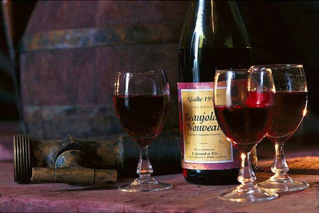 Бутылка Beaujolais nouveau и три бокала с вином
