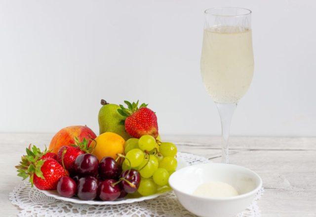 бокал с шампанским и фрукты в тарелке