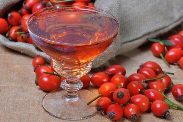 настойка шиповника в бокале и ягоды